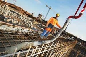 Worker guiding a concrete pump